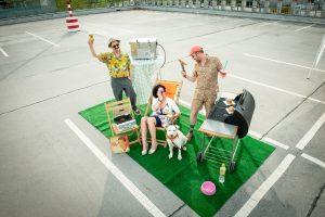 """Das Ergebnis des Fotoshootings """"Platz ist in der kleinesten Parzelle"""": Rollrasen in einer Parklücke, darauf feiern drei Menschen und ein Hund eine Grillparty."""