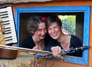 Zwei Frauen schauen durch ein blau gerahmtes Fenster, lachen und halten einen Bogen und eine Klarinette in den Händen