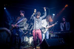 Drei Männer auf einer Bühne im Spotlight, rundum dunkel, Mikrophone, E-Gitarren und Lautsprecher