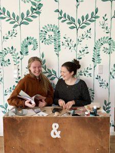Zwei Frauen vor einer grün gemusterten Tapete, an einem Holztisch mit weißem &-Zeichen und Büchern in der Hand