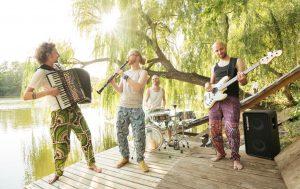 Drei Männer mit Akkordeon, Klarinette und E-Gitarre auf einem Steg an einem See, im Hintergrund Sonne, die durch eine Weide scheint