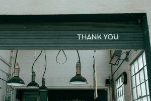 Garagentor Aufschrift Thank You Danke dahinter Raum im Industrial Stil mit rustikalen Deckenlampen und großen Fenstern Stil wie in der KUFA