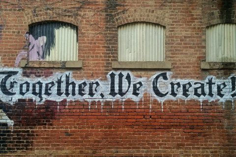 "Backstein-Wand mit Graffiti ""Together We Create!"""