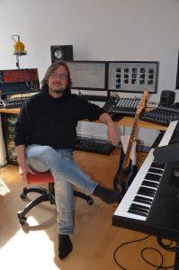 Ein Tonstudio zuhause mit Keyboard, Gitarre und Computer.