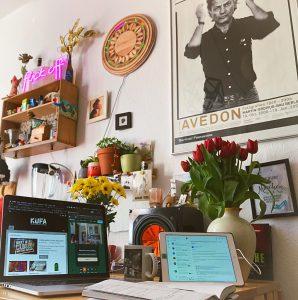 Klapprechner, Tablet, Notizbuch, rote Tulpen, gelbe Blumen, Richard Avedon Poster und viel Klimbim.