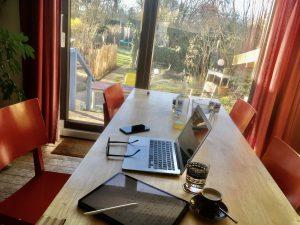 Ein Klapprechner, ein digitaler Notizblock, ein Handy und Getränke auf einem Tisch mit Blick in den Garten.