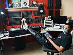Samet DJ Uncle S im heimischen Tonstudio, Füße hochgelegt und Mundschutz aufgesetzt